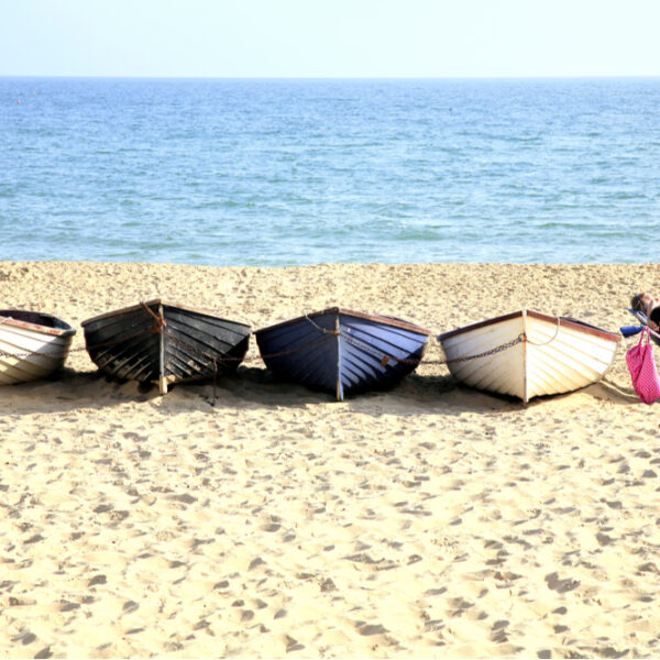 couple relax by row of boats on Bournemouth beach